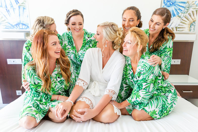bride and her bridal party laugh together on the bed before getting dressed for the wedding day in montego bay jamaica