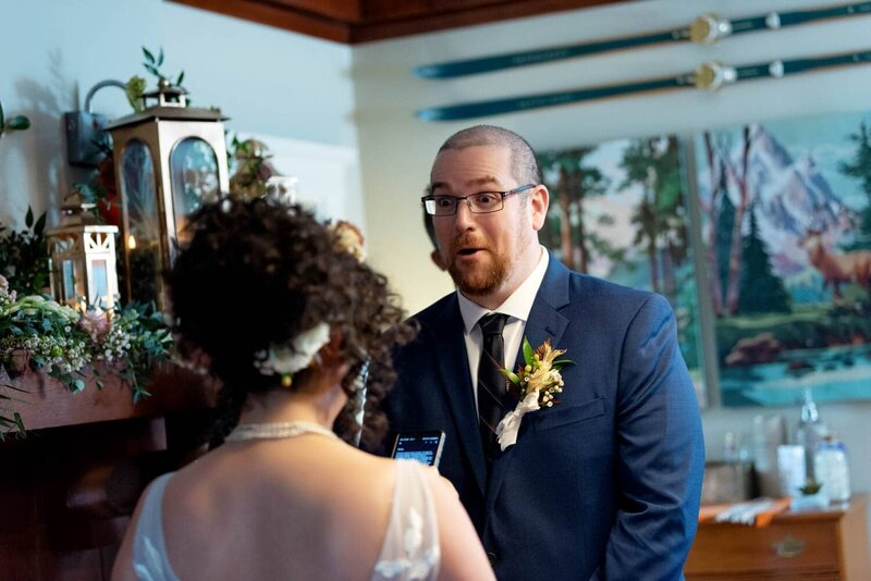 a groom makes a surprised expression as the bride reads her wedding vows