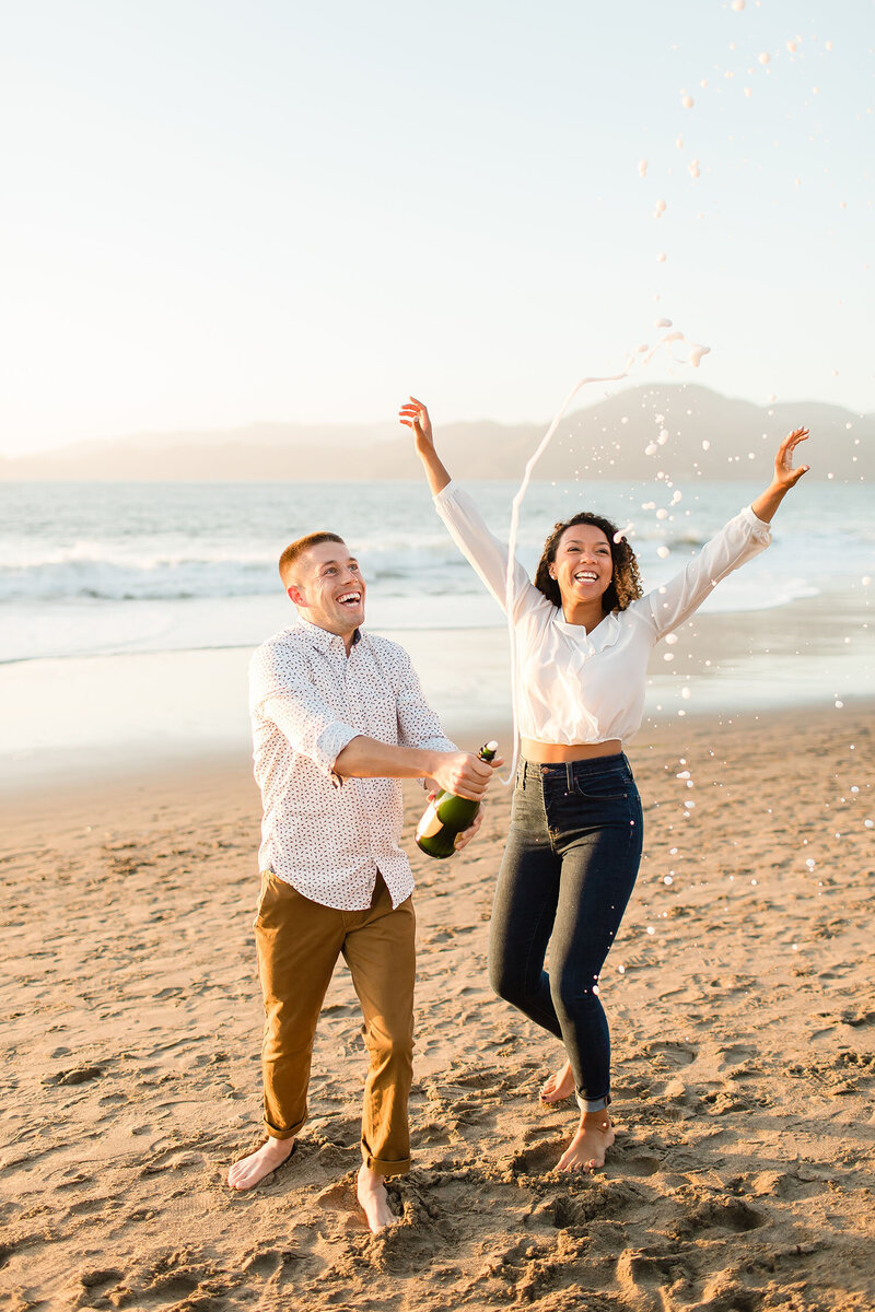 Engaged couple popping champagne on Baker Beach in San Francisco, California. Wedding photo taken by Cheers Babe Photo.