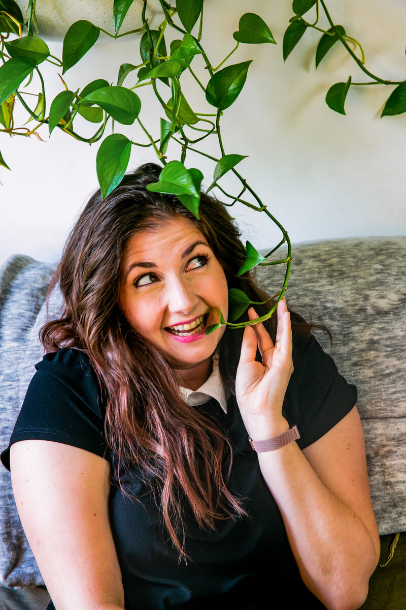 Woman smiles on her sofa while holding leaves of wall climbing plant