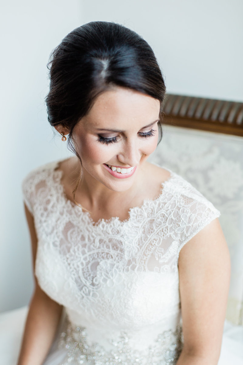 Dark haired bride in lace wedding gown posing for bridal portrait