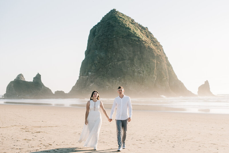 Couple holding hands and walking in front of Haystack Rock at Cannon Beach