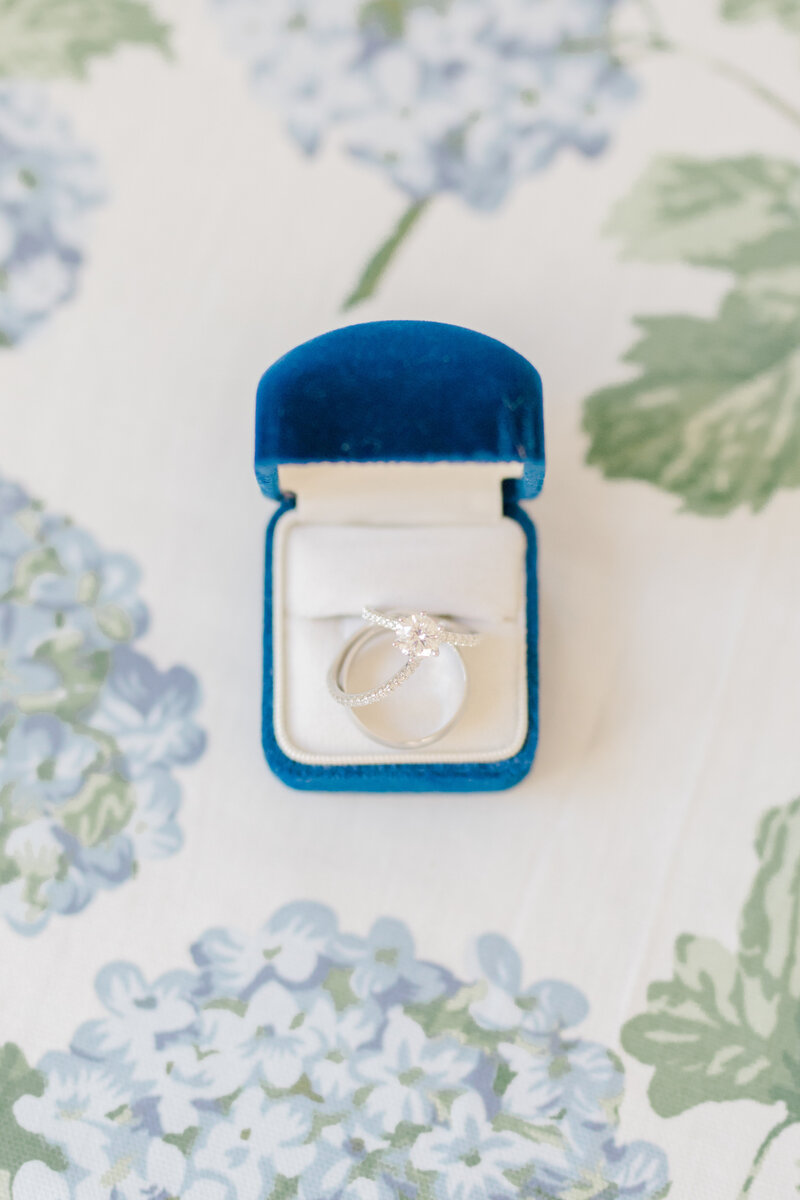 wedding rings in blue velvet box on floral table at Inn at Perry Cabin wedding in St Michaels Maryland by Costola Photography