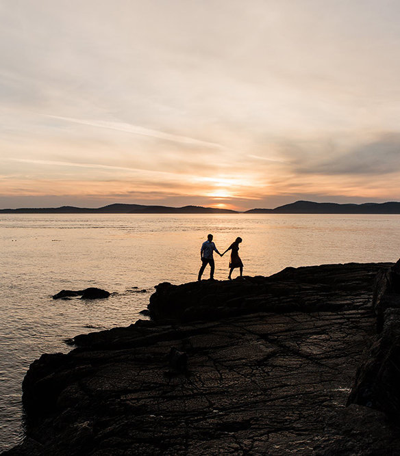 a woman leads her partner across a beach as the sun sets during their engagement session in anacortes