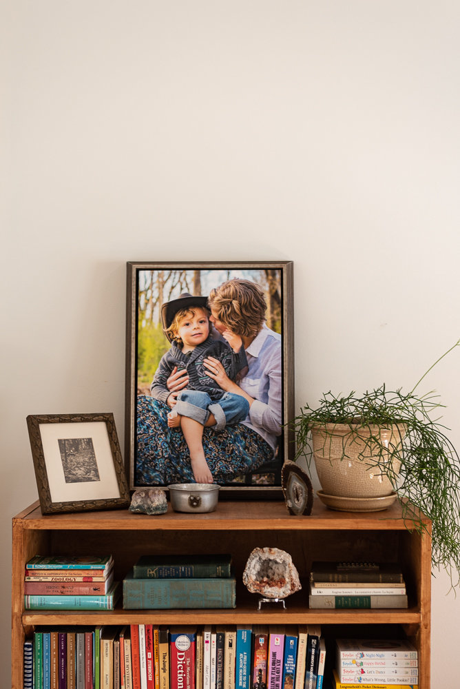 A portrait of a mother holding her son sits on a shelf.