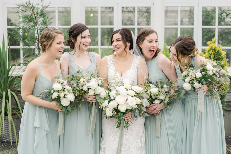 bridesmaids and bride look at eachother and laugh