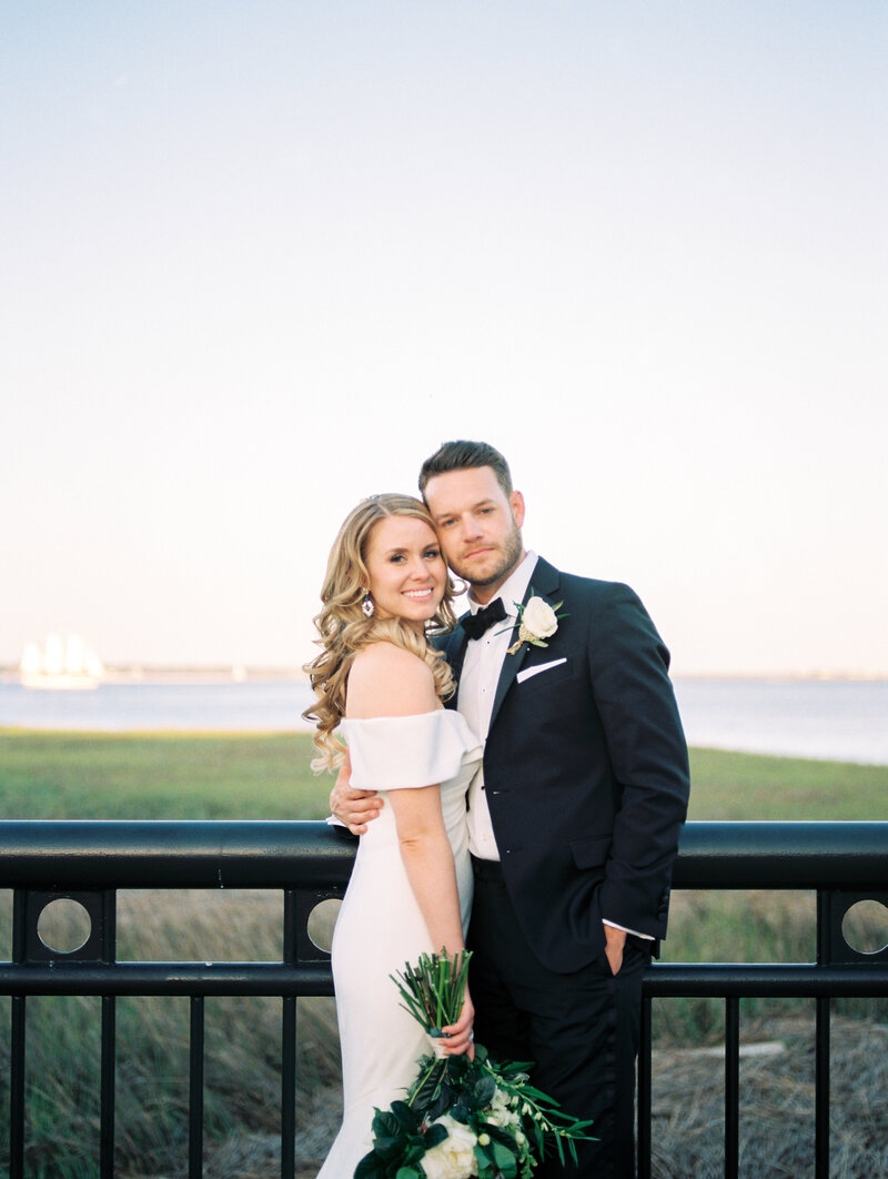 Bride and groom embrace on their wedding day on the Charleston waterfront