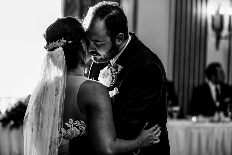 Groom leans in to whisper to bride during first dance at the George Washington hotel wedding