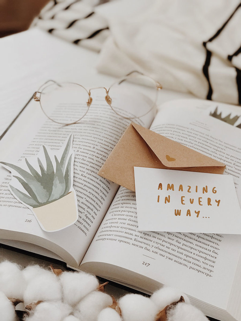 Glasses, book and card flat lay