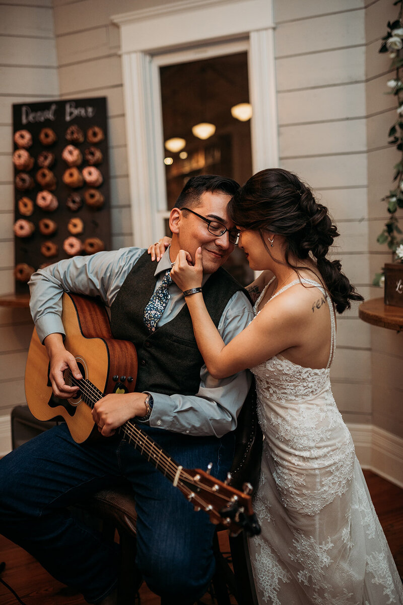 Groom playing guitar for wife