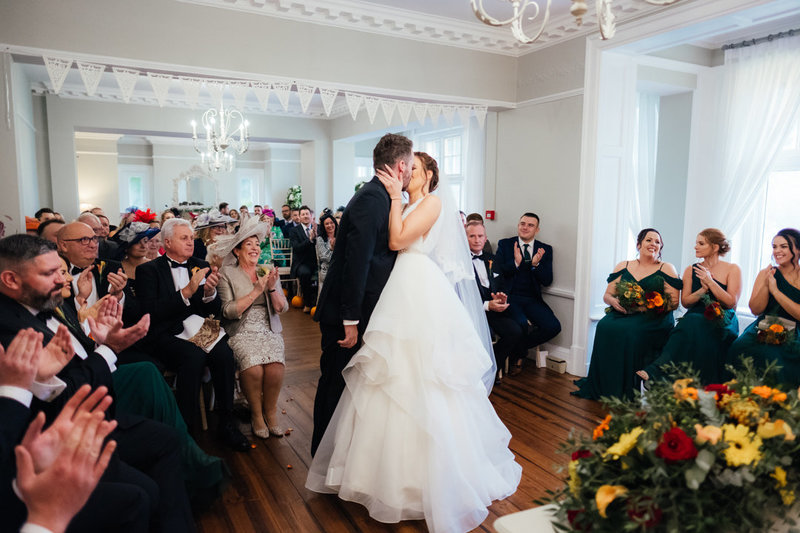 bride and groom kiss at the end of their wedding ceremony at Ashton Lodge Country House wedding venue.  Their guests look on clapping and cheering at their first wedded kiss.