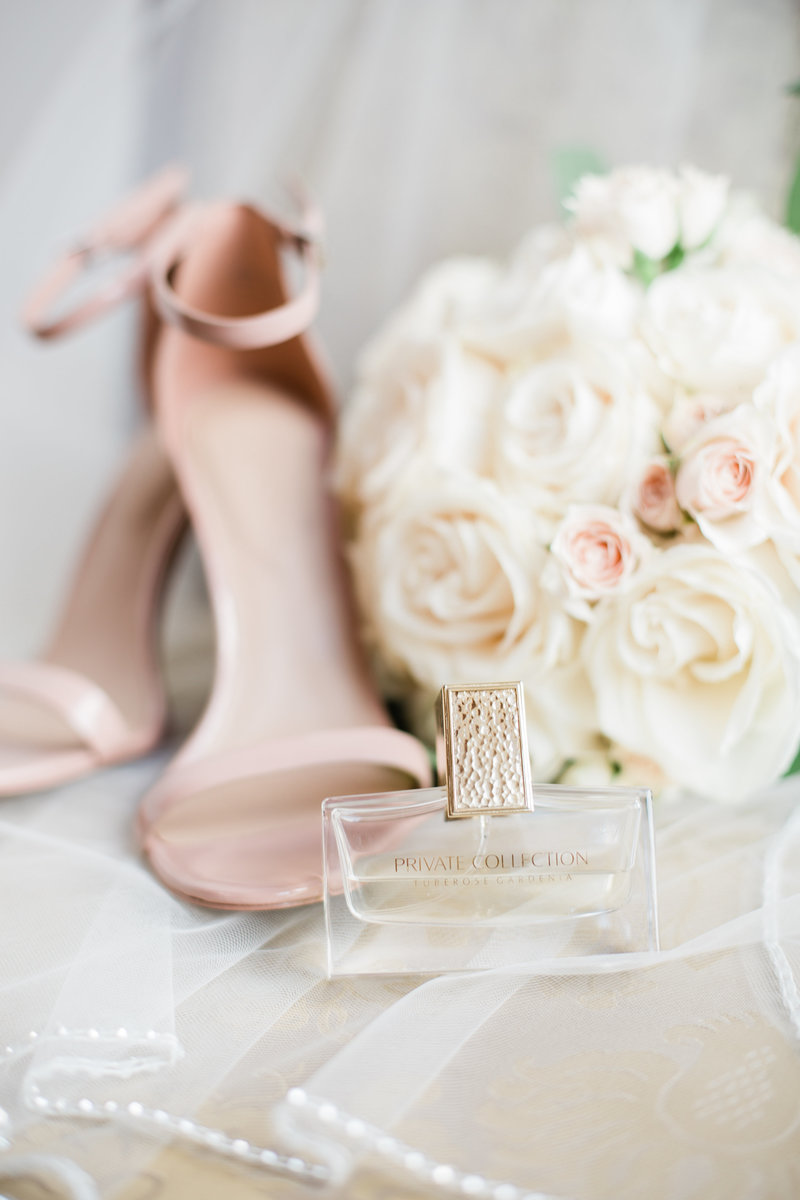 Pastel pink heels with white rose bouquet and perfume bottle