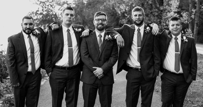 Groom stands with his groomsmen on the walking path at Presque Isle State Park