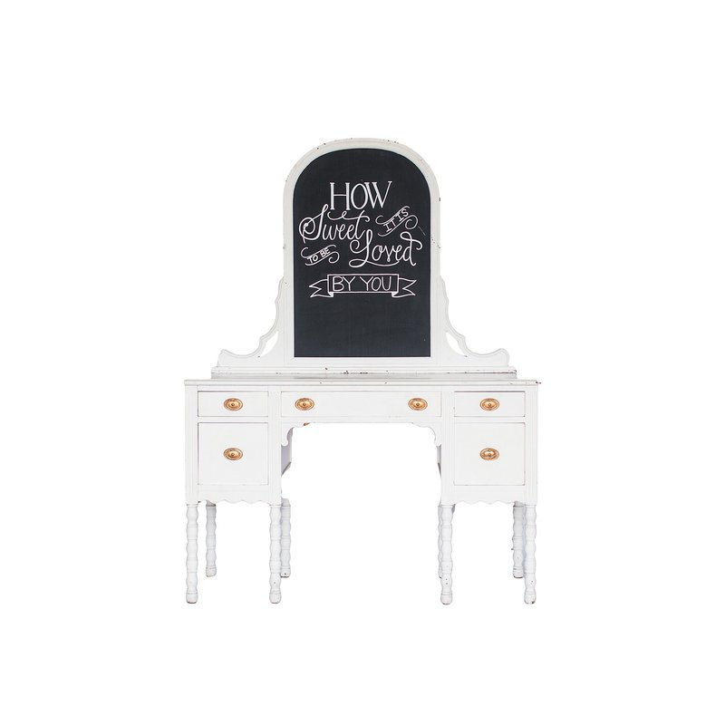 "White vanity with gold hardware and chalkboard that reads ""How sweet it is to be loved by you""."
