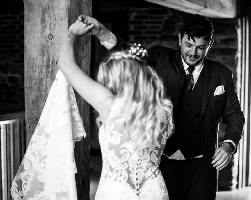 Groom twirls bride around during first look photos at Quincy Cellars