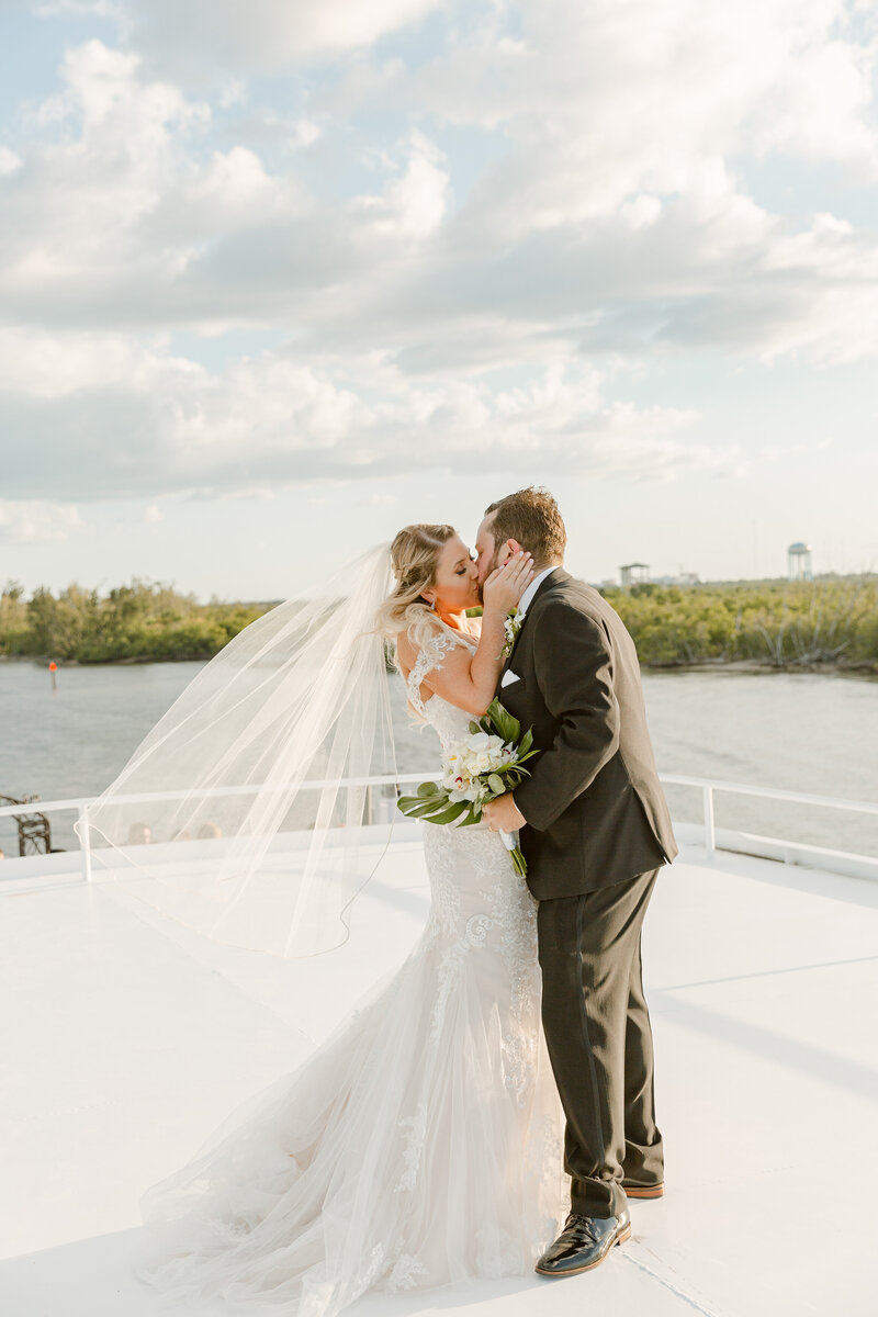 Bride and groom kiss on the deck of a yacht on their wedding day in Florida
