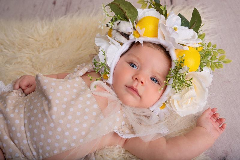 Baby girl wearing a lemon flower bonnet. Milestone photography session