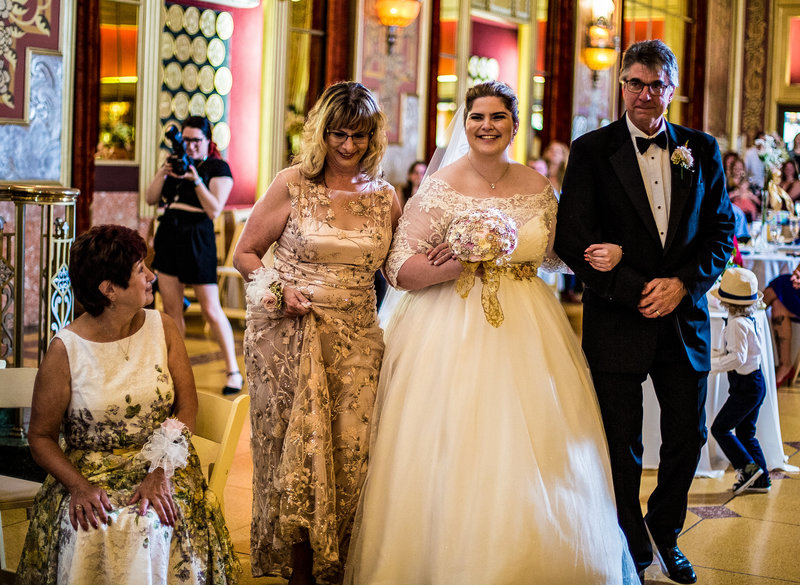 Bride's parents escort her down the aisle for her wedding at the Warner Theatre