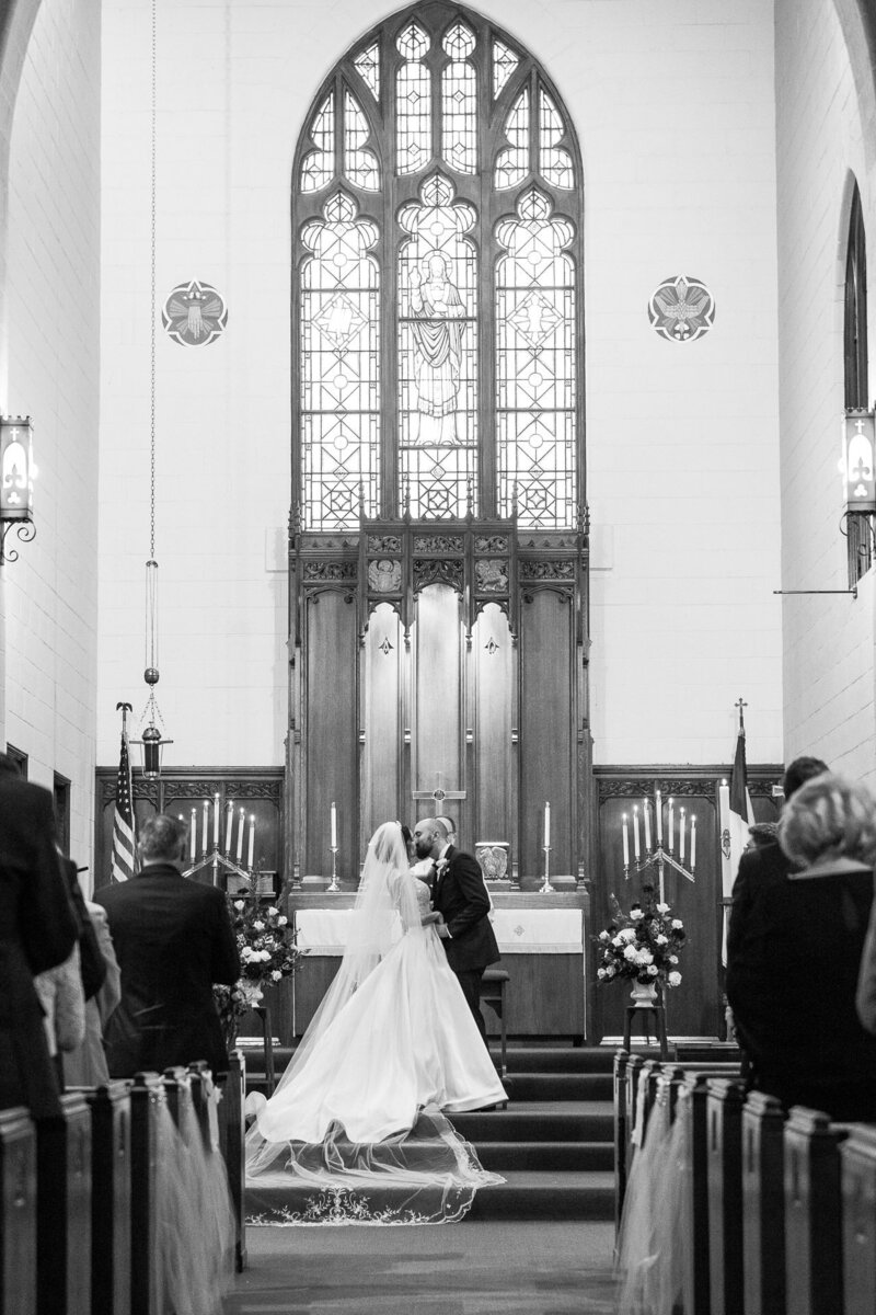 bride and groom first kiss at trinity lutheran church in port huron wedding