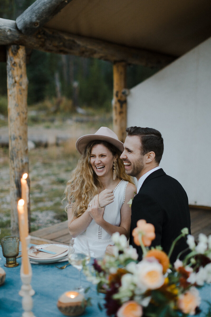 A newlywed couple sits at their wedding table and laughs