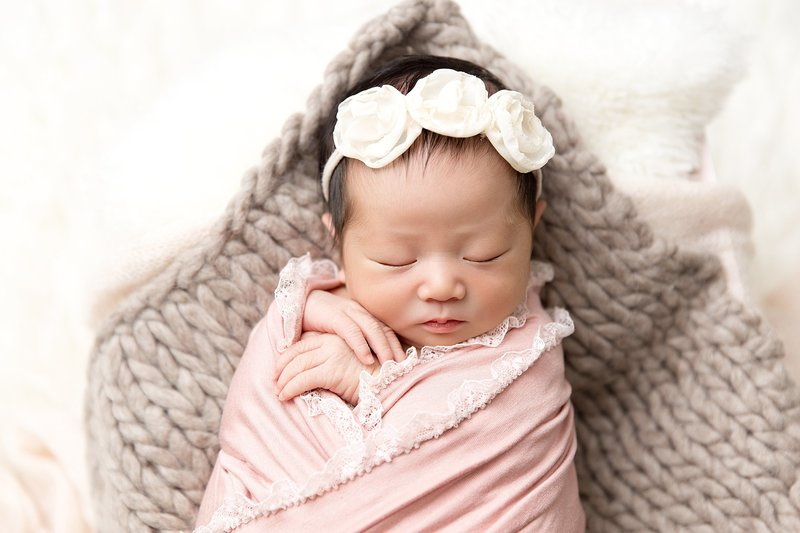 newborn with pink lace wrap