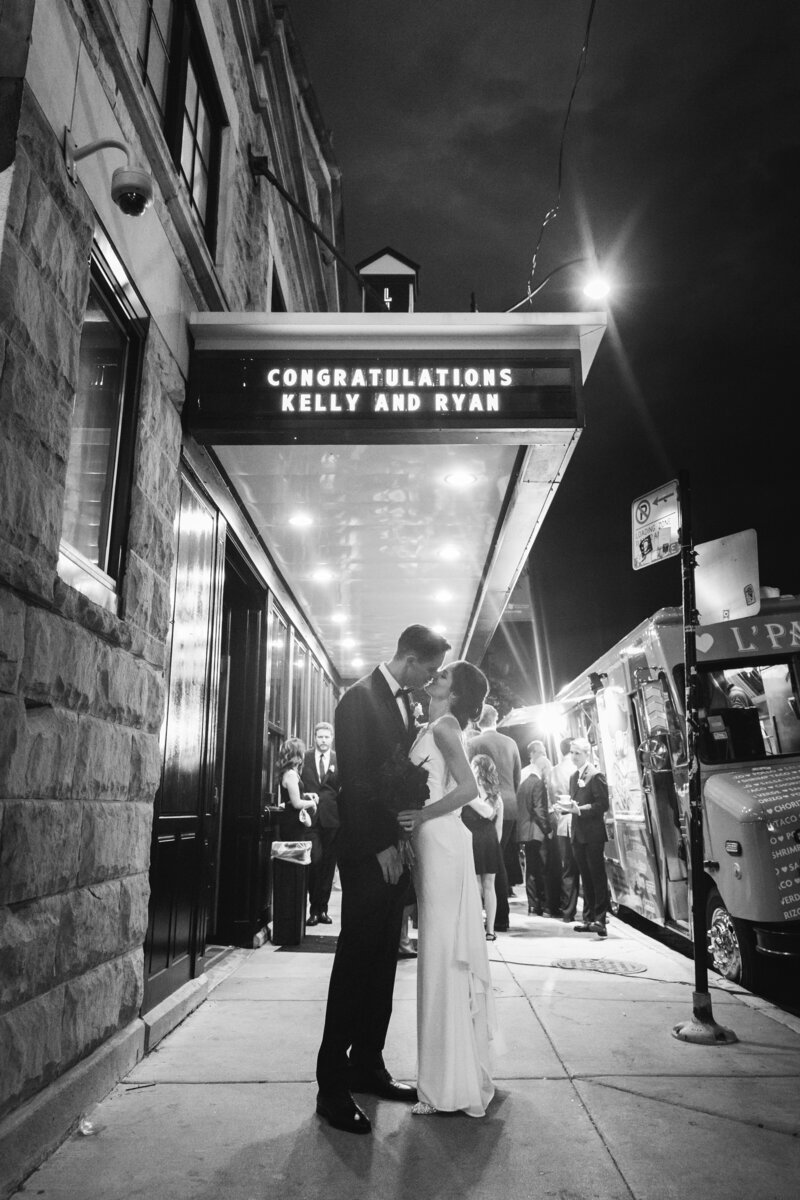 Bride and groom kissing in front of Lincoln Hall in Chicago