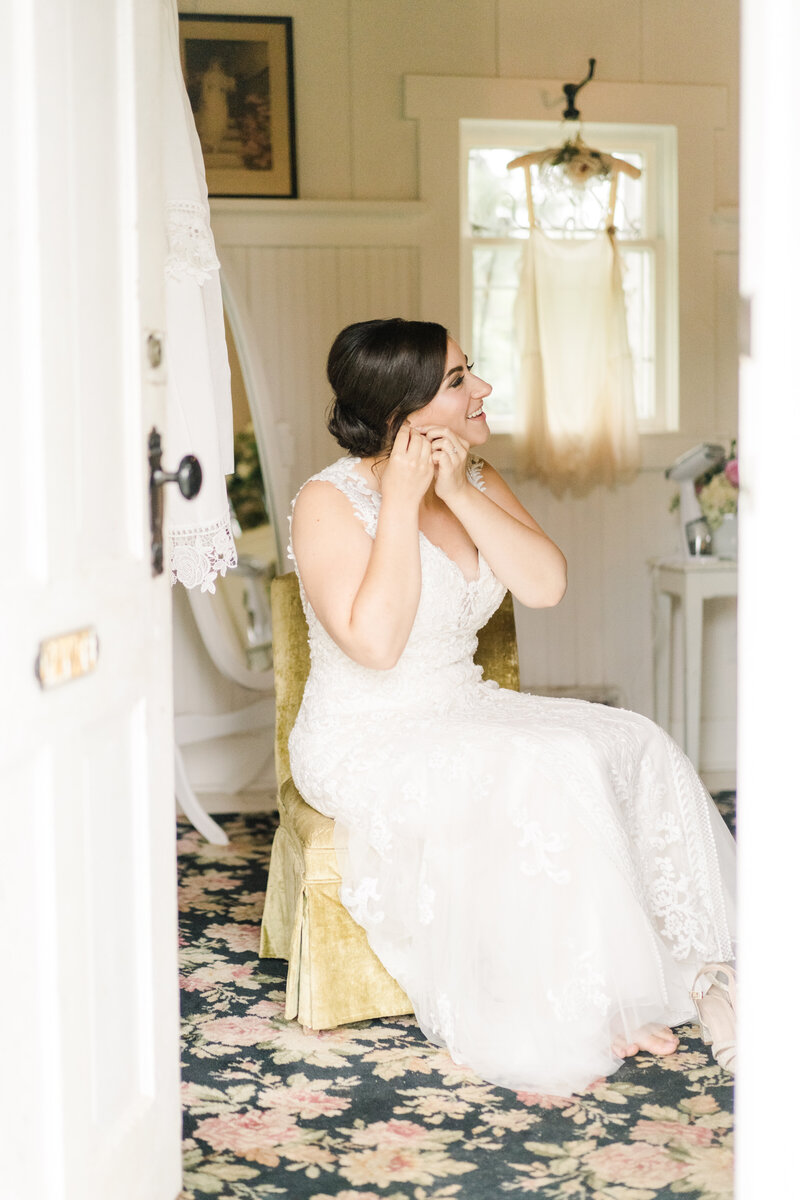 bride sitting down and putting earrings in
