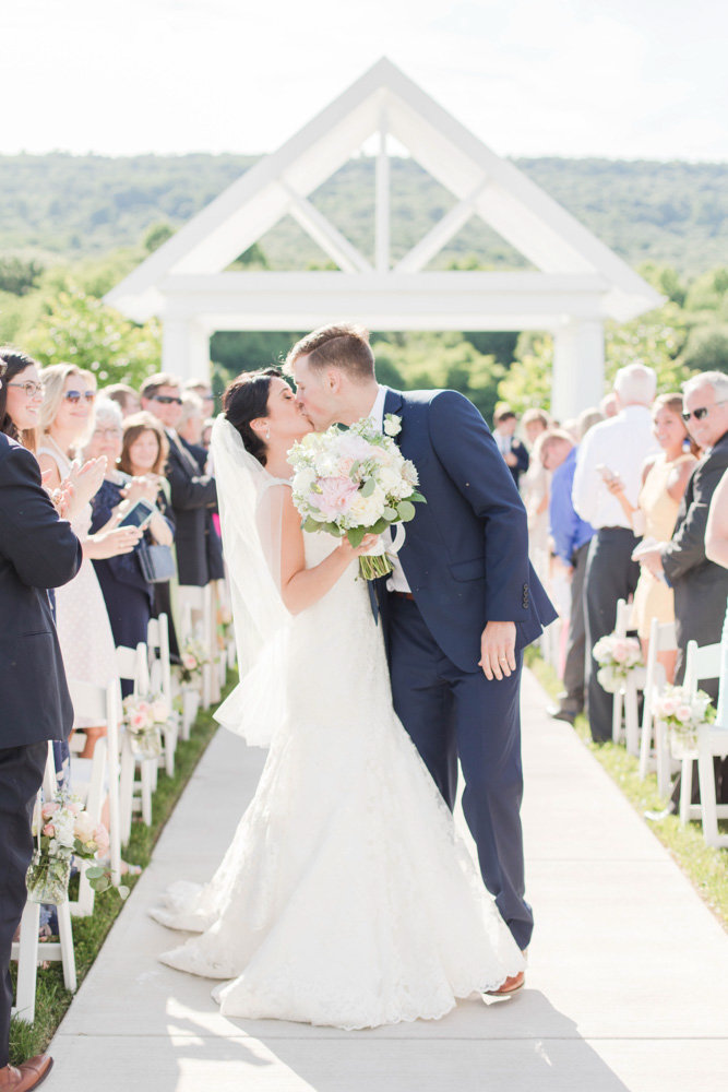 bride and groom kissing during ceremony at springfield manor winery and distillery wedding by costola photography