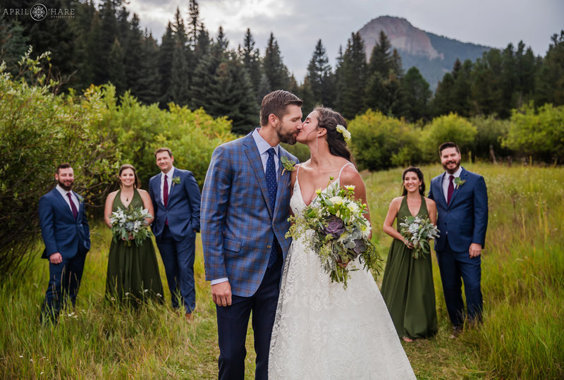 Bride and Groom kiss in mountain meadow at Mountain View Ranch in Pine CO