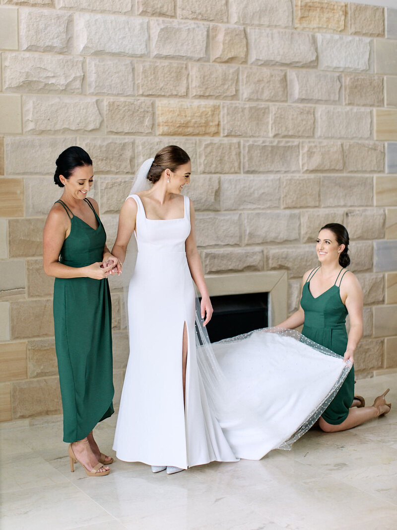 Bride standing in front of a sandstone wall having her wedding dress adjusted by her bridesmaids