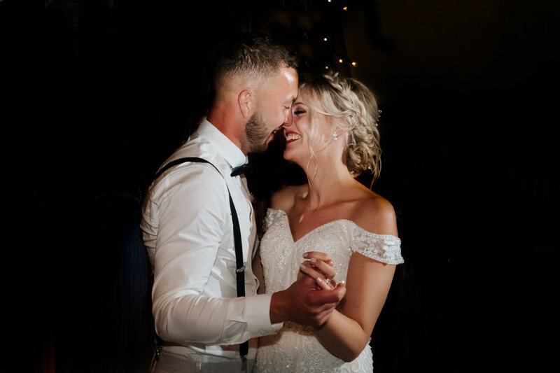 Newly wed husband and wife, embrace closely whilst performing their first dance.  she smiles as she looks into his eyes.
