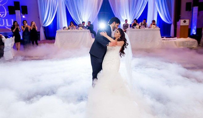 husband dipping his bride during the first dance on the clouds