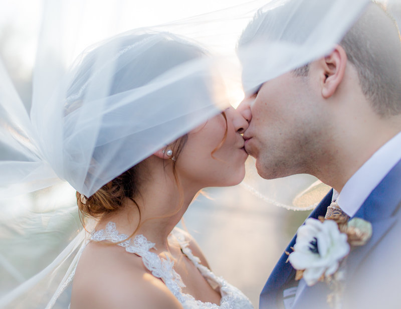 bride and groom under the veil kissing for naples wedding photos