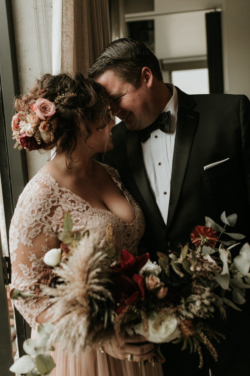 Bride and groom wedding portrait shot with bride in blush wedding dress and floral headpiece and dramatic bridal bouquet