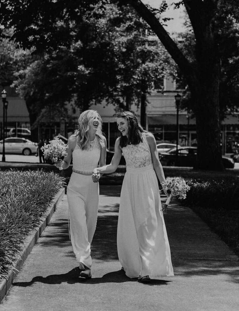 LGBTQ couple strolling in front of the courthouse on their wedding day.