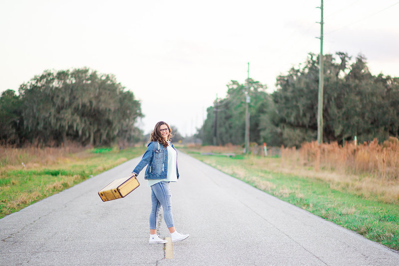 A senior poses with her suitcase in the street in Wauchula, Florida.