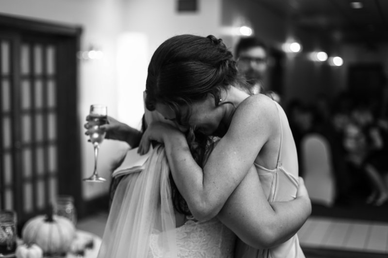 Bridesmaid cries on bride's shoulder during Nick's Place wedding reception