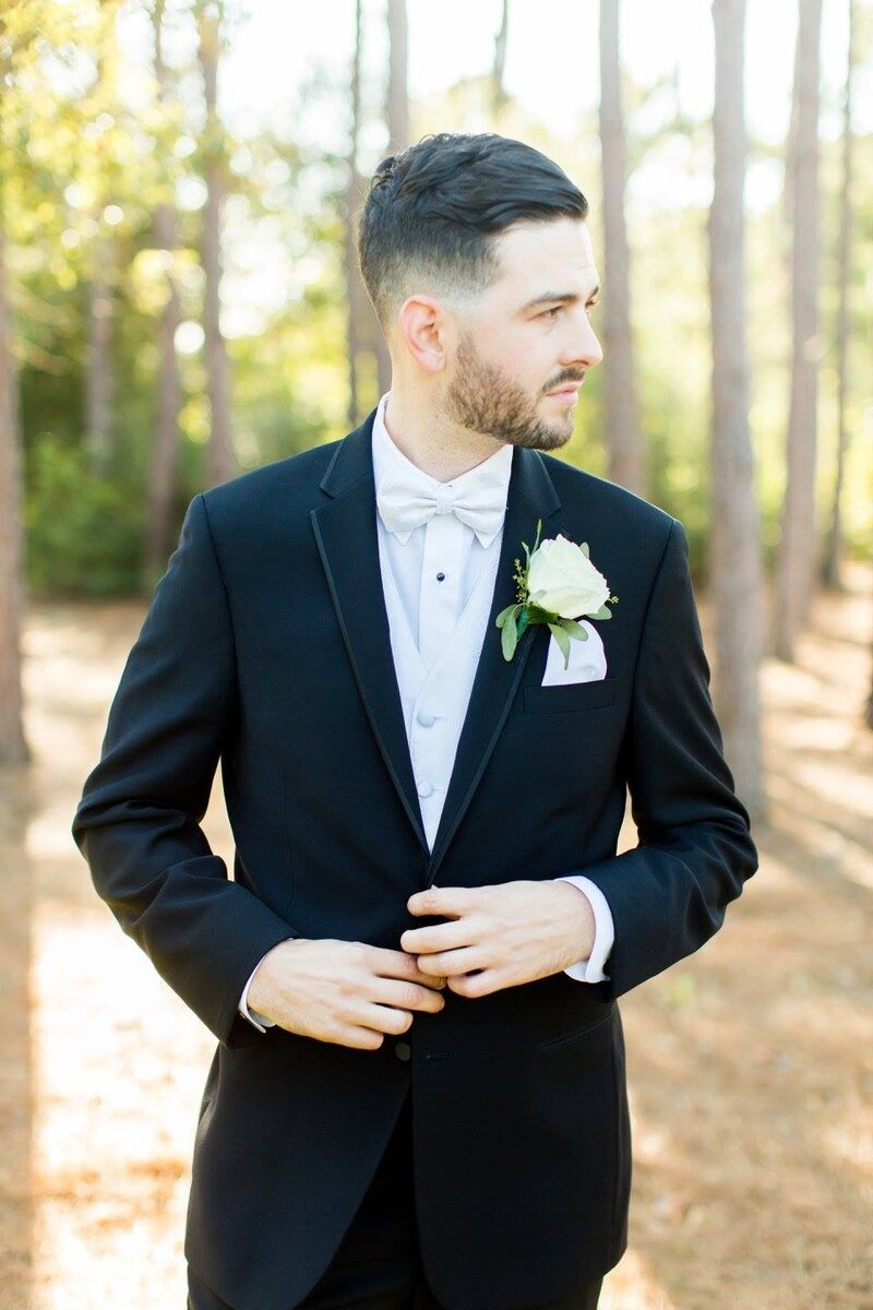 handsome dark haired groom in a black tuxedo with a white bowtie