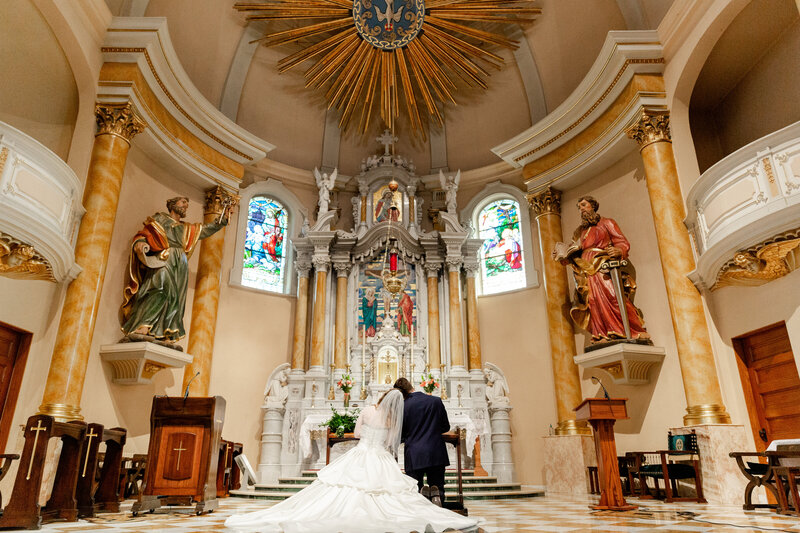 Bride and groom kneeling before the altar in catholic church