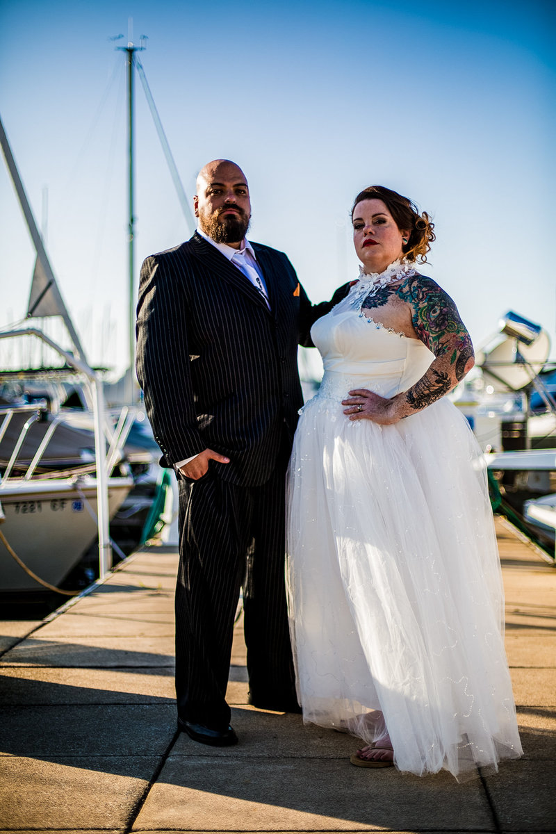 Couple poses among the boats at their Erie Yacht Club wedding