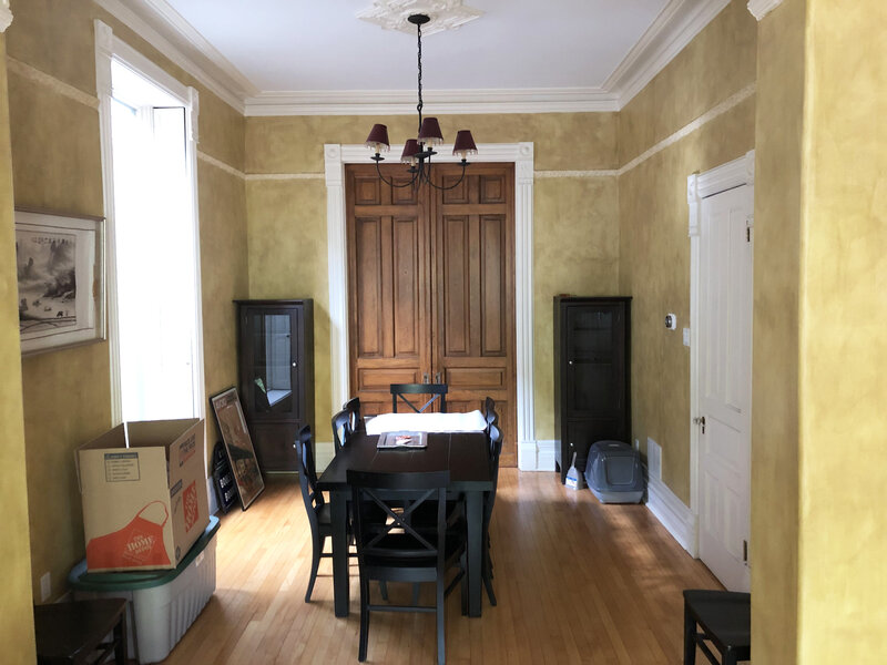 Superior dining room before staging with black wood dining table and chairs large wooden doors black wood cabinets litter box storage totes and boxes