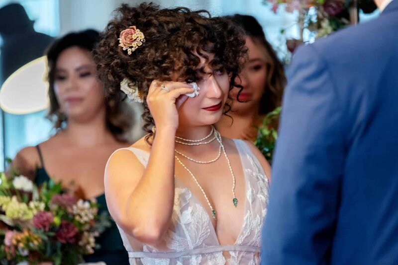 a bride wipes a tear away from her face during a wedding ceremony