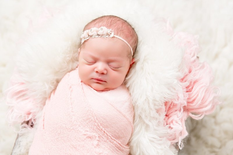 newborn wrapped in pink with white flower headband