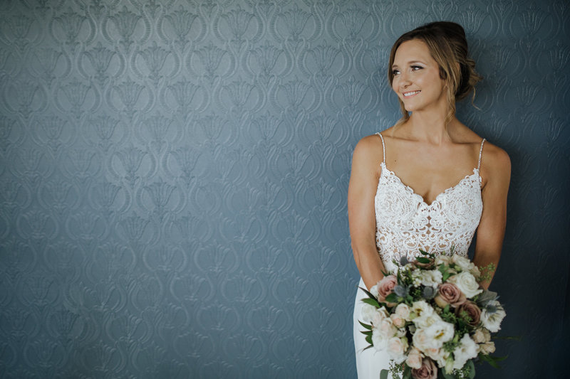 A bride stands in front of a blue floral wall with her bouquet at Autumn Ridge Farm in Franklin, Tennessee.