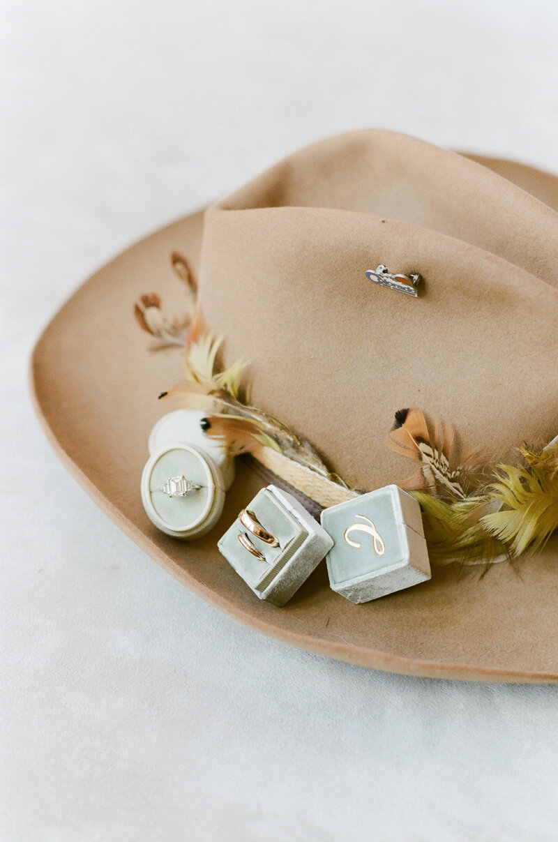 Wedding accessory details, a feather trimmed tan cowboy hat and wedding rings in decorative blue boxes