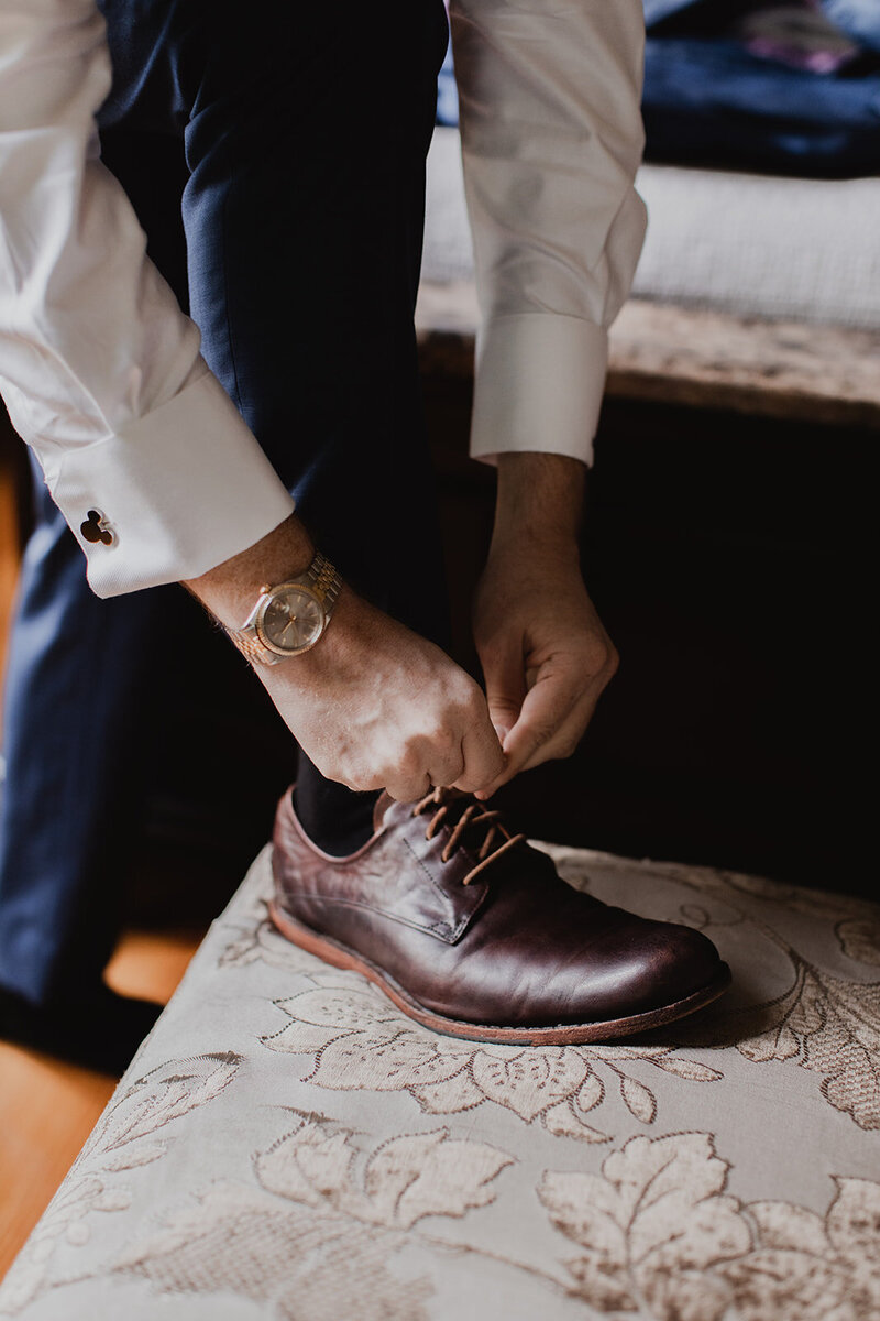 Groom putting on shoes, watch detail