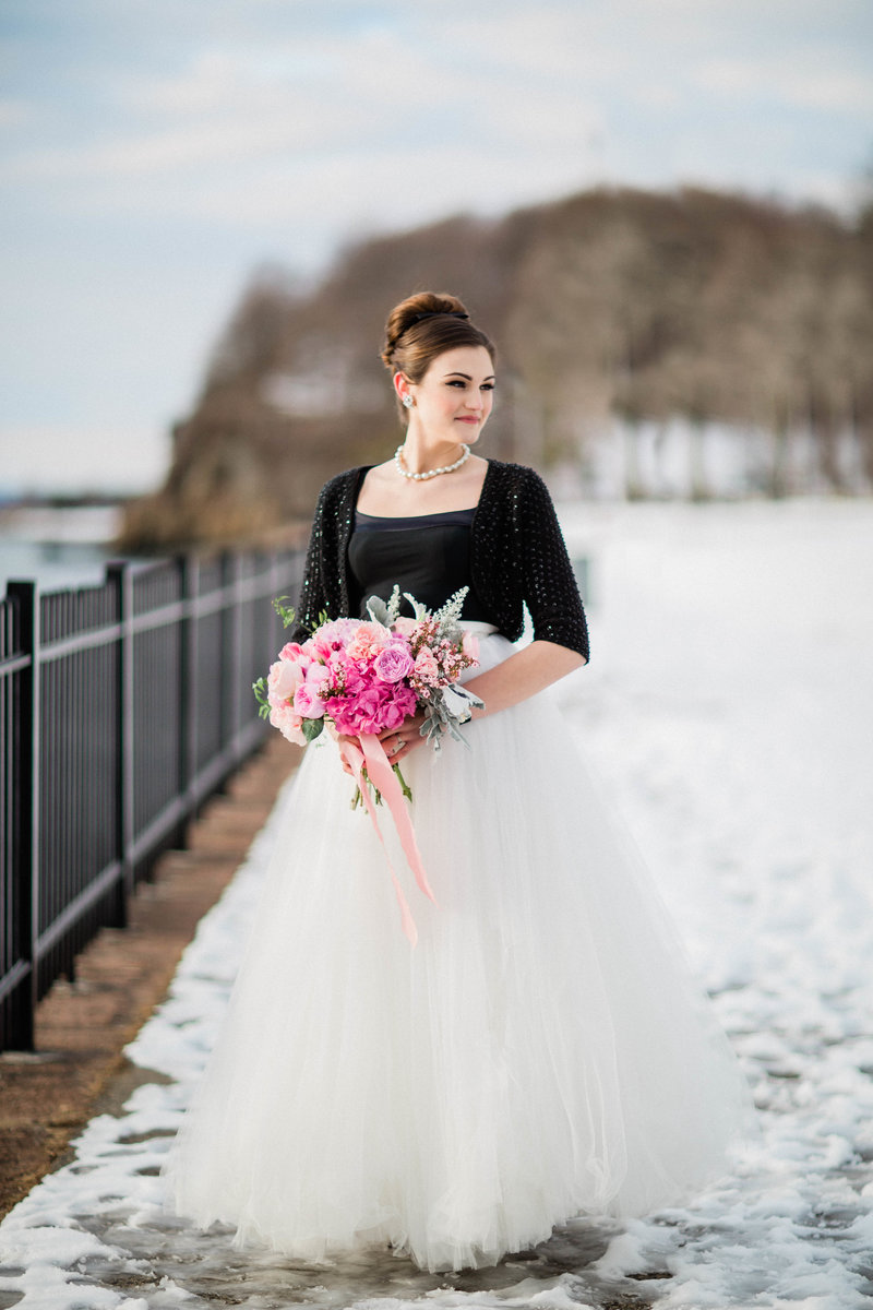 Young woman with dark brown hair in updo standing in the snow holding pink peony bouquet in white dress and black shawl