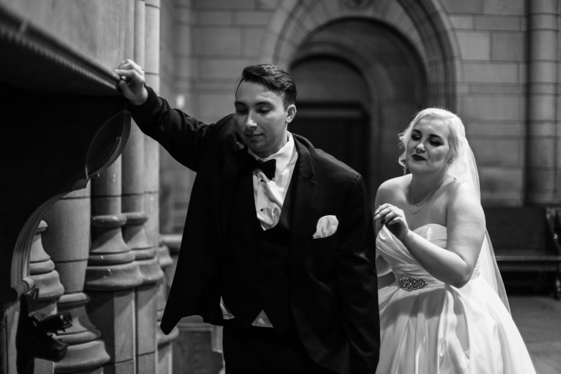 Bride taps groom on shoulder for first look portrait at Cathedral of Learning in Pittsburgh, PA