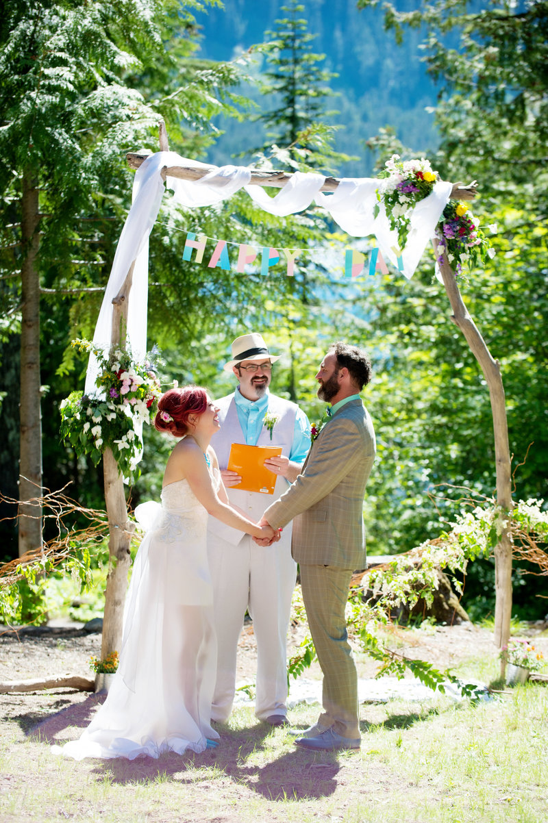 a couple says their vows in front of a colorful ceremony backdrop at lost lake