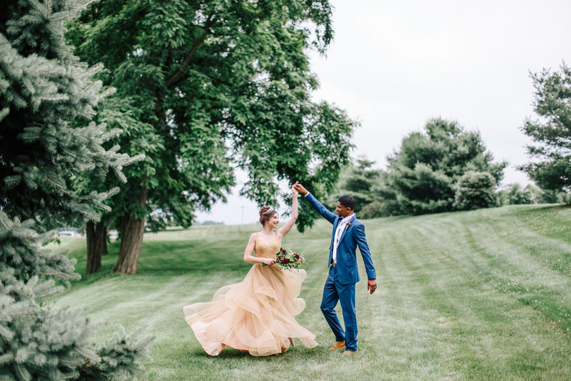 Bridge and groom twirling in a field